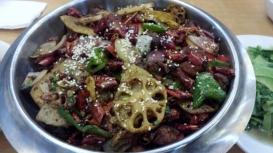 Typisch Sichuan Küche. Ein großer Topf mit viel Fleisch, Gemüse, Chilis und ganz viel Gewürzen.
