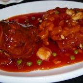 Mandarin Fisch, Knusprig frittierter Fisch ohne Gräten, Ananas, Erbsen und süß saurer Sauce. Besonders dabei ist, dass der Kopf und die Schwanzflosse nach oben gebogen werden, damit der Fisch einem Eichhörnchen gleicht.