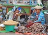 Zum Zeitvertreib liest eine Marktfrau der anderen vor.