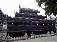 Shwenandaw Kyaung. Das Teakholzgebäude stand bis 1880 im Königspalast und diente dort als Königsgemach. König Thibaw ließ es 1880 nach dem Tod von König Mindon abreißen und als Kloster außerhalb der Palastmauern wieder aufbauen. Es ist somit das einzige original erhaltene Palastgebäude.