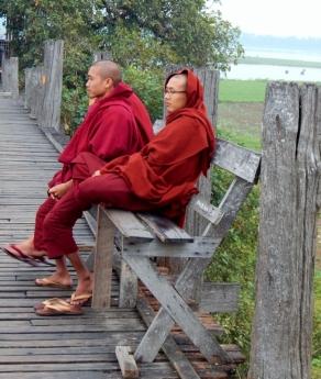 Mönche ruhen sich auf der Brücke aus und folgen gespannt einem Fußballspiel am Ufer.