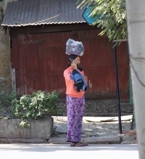 Eine Frau wartet auf den Bus. Handys gehören schon zur Grundausstattung in Myanmar.