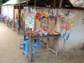 Ein kleiner einfacher Laden (Schulkiosk) an der Häuserecke. Die Kinder kommen mit dem Fahrrad zur Schule geradelt.