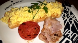 Die Hauptzutaten für ein ordentliches Frühstück im südlichen Afrika. Eier, Speck, Tomaten und Toast.
